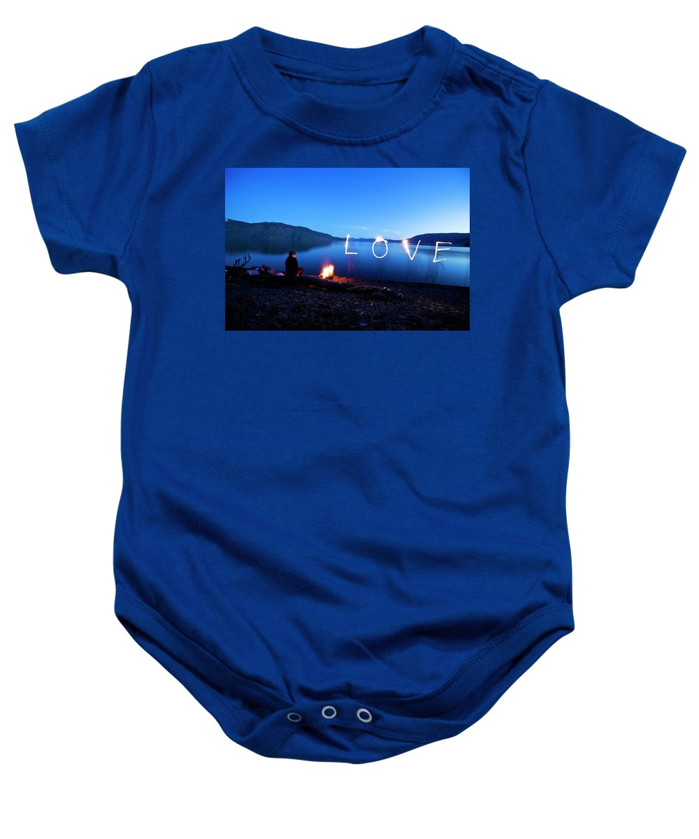 18-19 Years Baby Onesie featuring the photograph A Woman Sits Next To A Beautiful by Patrick Orton