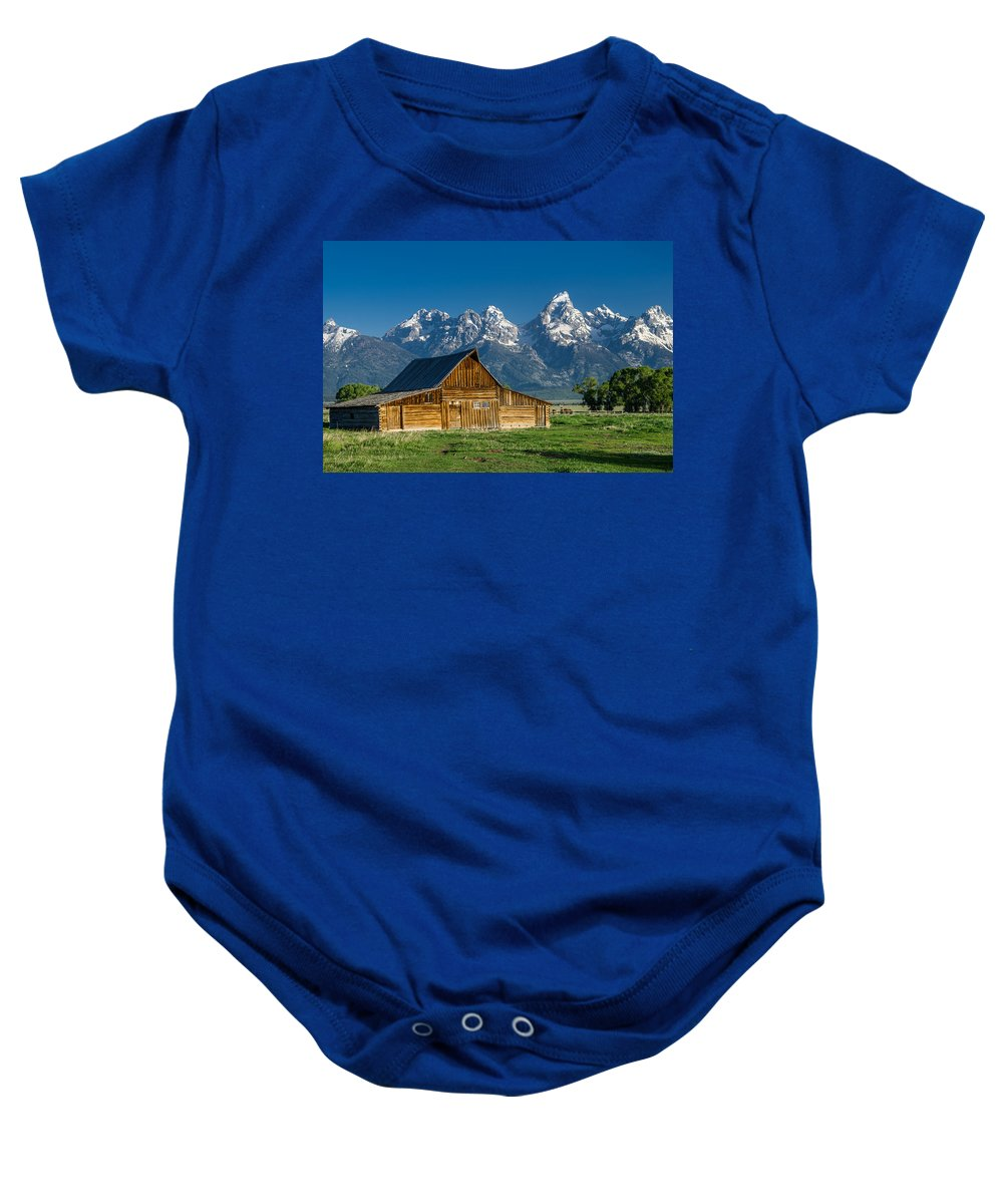 Mormon Row Baby Onesie featuring the photograph Molton Barn And Grand Tetons by Greg Nyquist