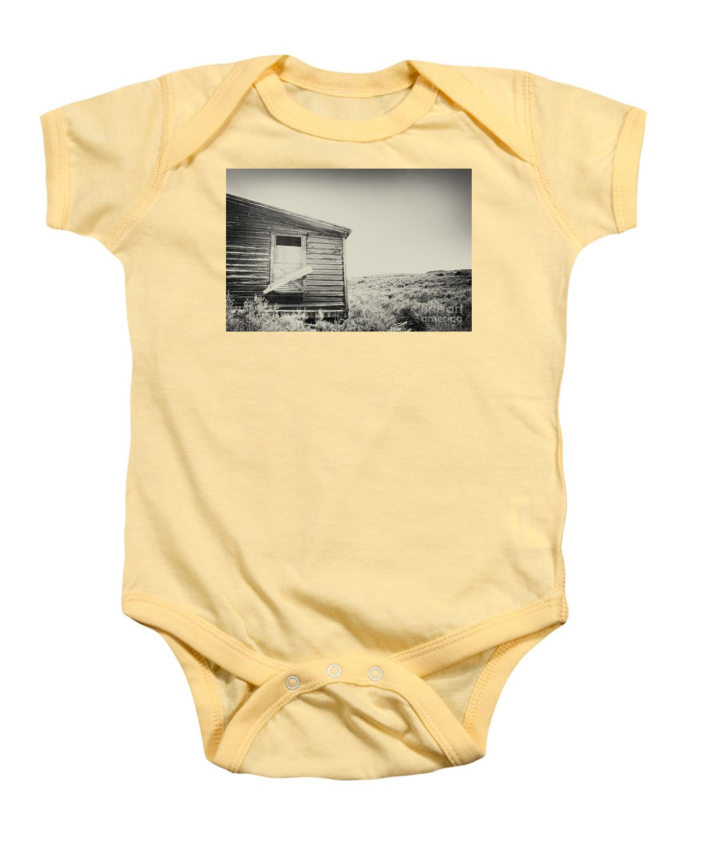 Structure; Wood; Wooden; Country; Countryside; Desert; Deserted; Worn; Abandoned; Boards; Ruins; Boarded Up; Grasses; Hills; House; Home; Sepia; Rural; Vast; Dirt; Window; Sky; Vintage; Antique Baby Onesie featuring the photograph Boarded by Margie Hurwich