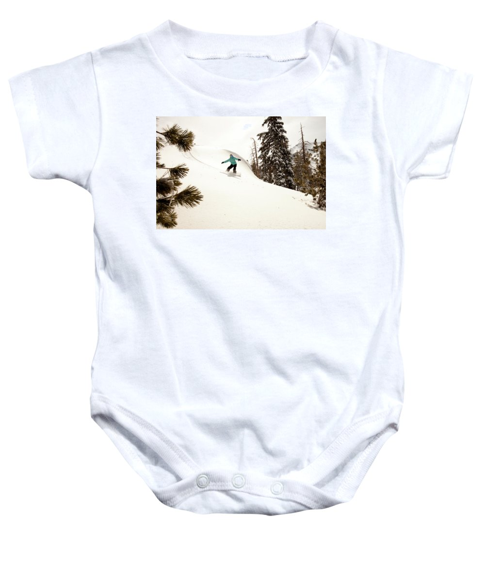 California Baby Onesie featuring the photograph A Female Snowboarder Lays Out Some by Kyle Sparks