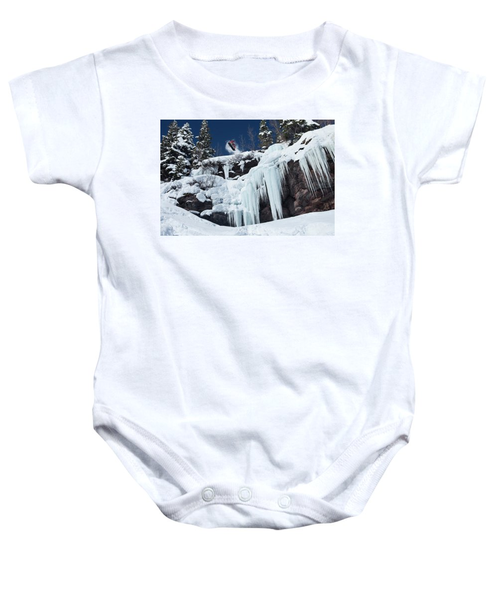 Action Baby Onesie featuring the photograph A Snowboarder Jumps Off An Ice by Patrick Orton