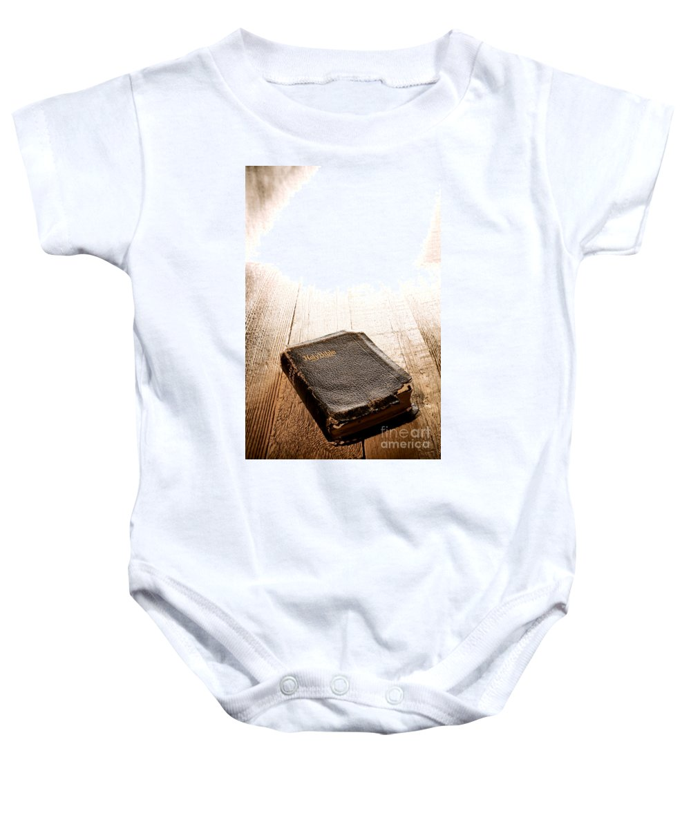 Holy Baby Onesie featuring the photograph Old Bible In Divine Light by Olivier Le Queinec