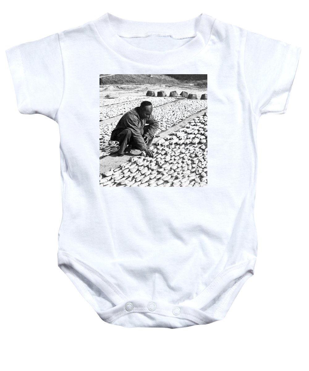 Chinese Baby Onesie featuring the photograph Chinese Man Drying Fish On The Shore - C 1902 by International Images