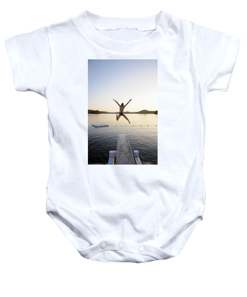 Arms Outstretched Baby Onesie featuring the photograph A Swimmer Jumps Off A Diving Board by James MacDonald