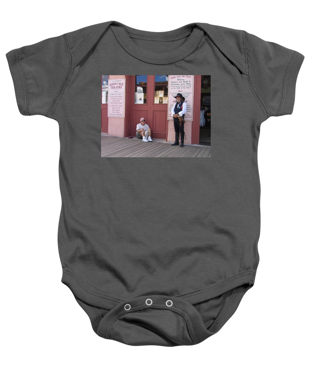 Dog Re-enactor Bird Cage Theater Tombstone Arizona Rendezvous Of The Gunfighters Baby Onesie featuring the photograph A Dog And A Re-enactor Rest In The Front Of The Bird Cage Theater Tombstone Arizona by David Lee Guss
