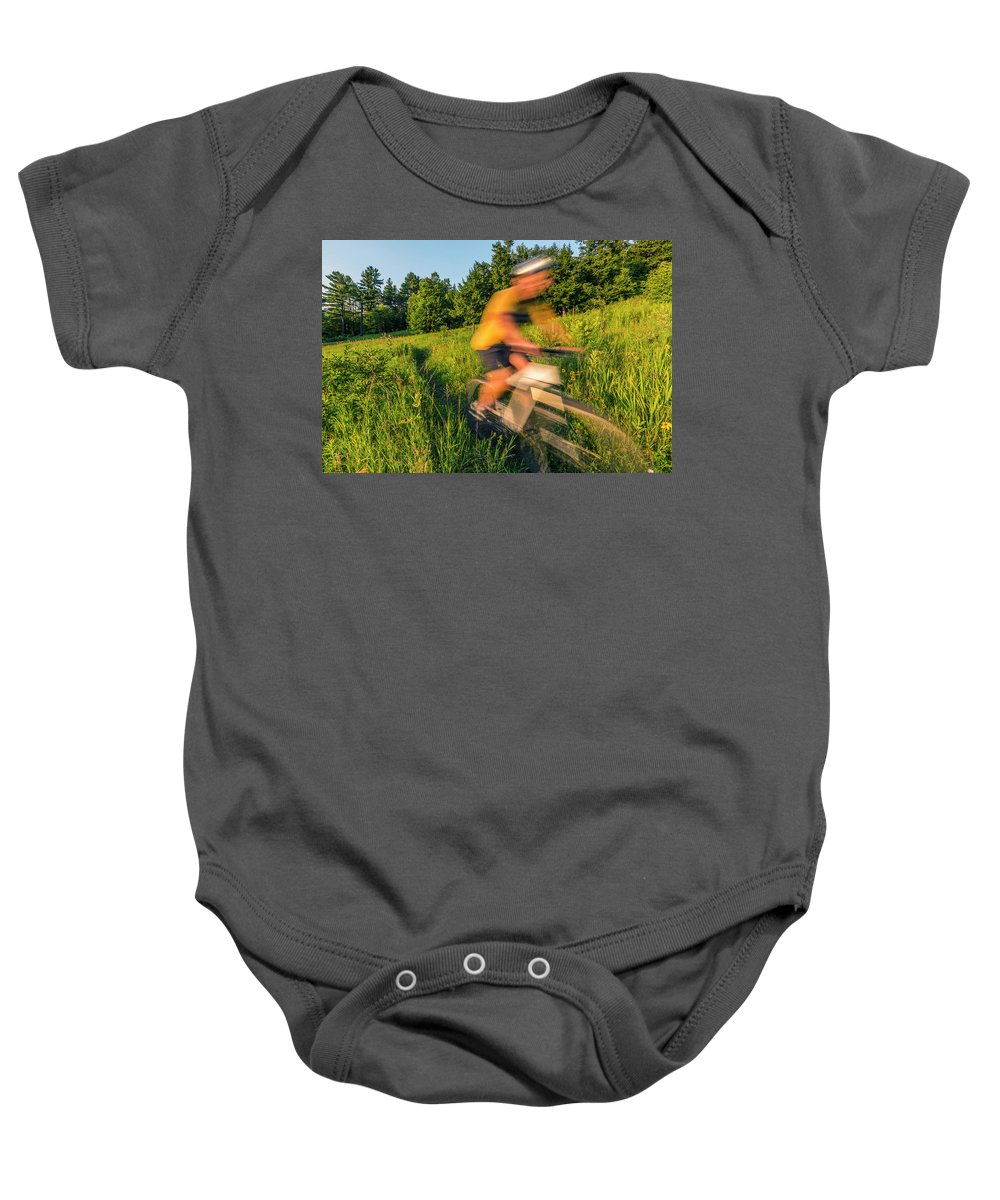Speed Baby Onesie featuring the photograph A Man Mountain Biking In A Field by Jerry Monkman