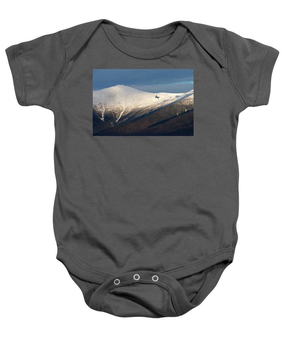 Airplane Baby Onesie featuring the photograph A Plane Flies In The Distance Over Mt by Jose Azel
