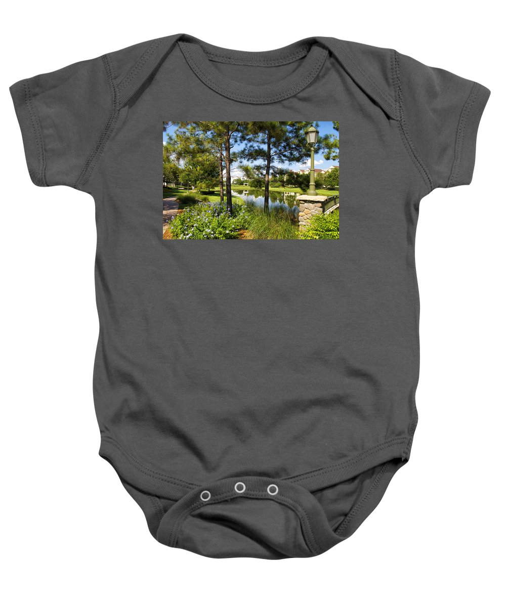 Pond Baby Onesie featuring the photograph A Tranquil Pond At Walt Disney World by Thomas Woolworth