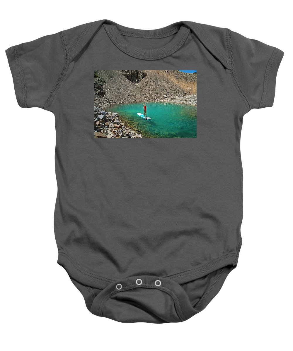 Sup Baby Onesie featuring the photograph A Young Male Paddleboarding On A Small by Brandon Huttenlocher