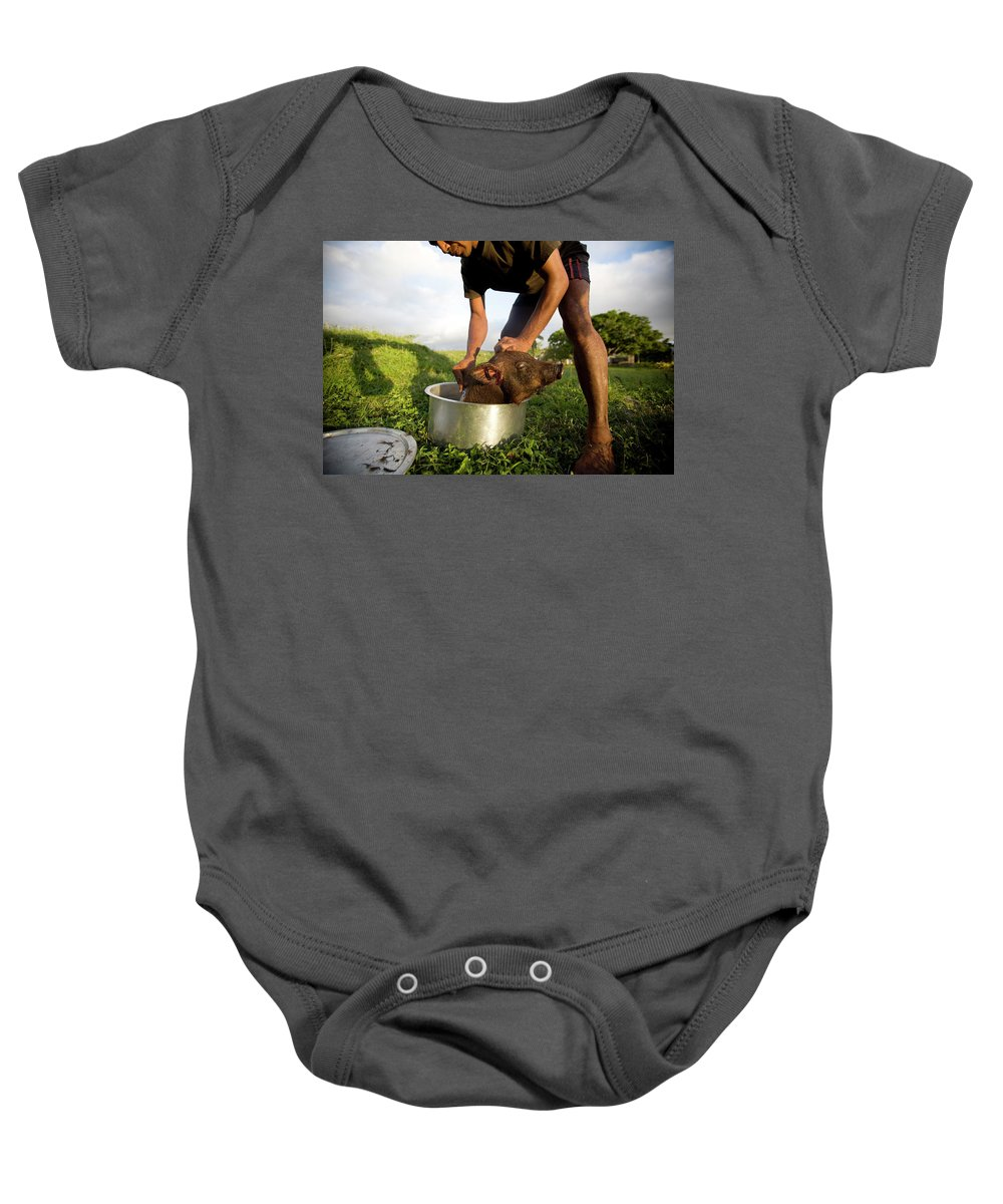 20s Baby Onesie featuring the photograph A Young Man Cleans A Freshly by Michael Hanson