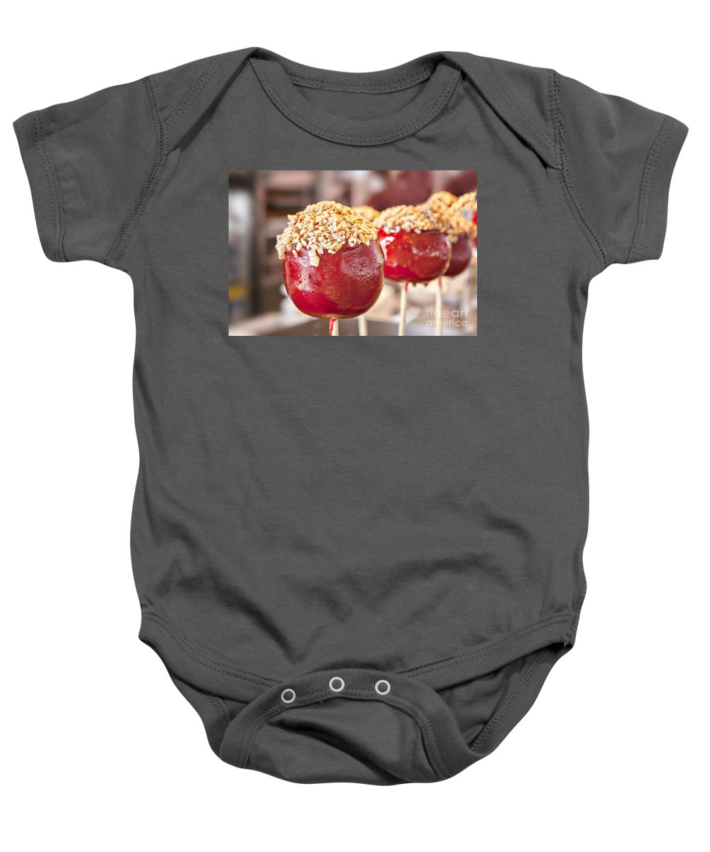 Candy Baby Onesie featuring the photograph Candy Coated Apple by Sophie McAulay