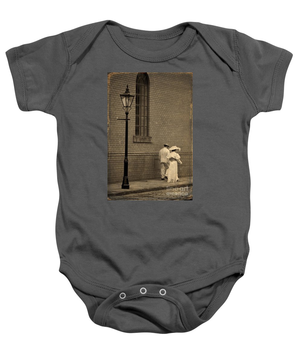 Edwardian Baby Onesie featuring the photograph Edwardian Couple Walking On A Cobbled Street by Lee Avison