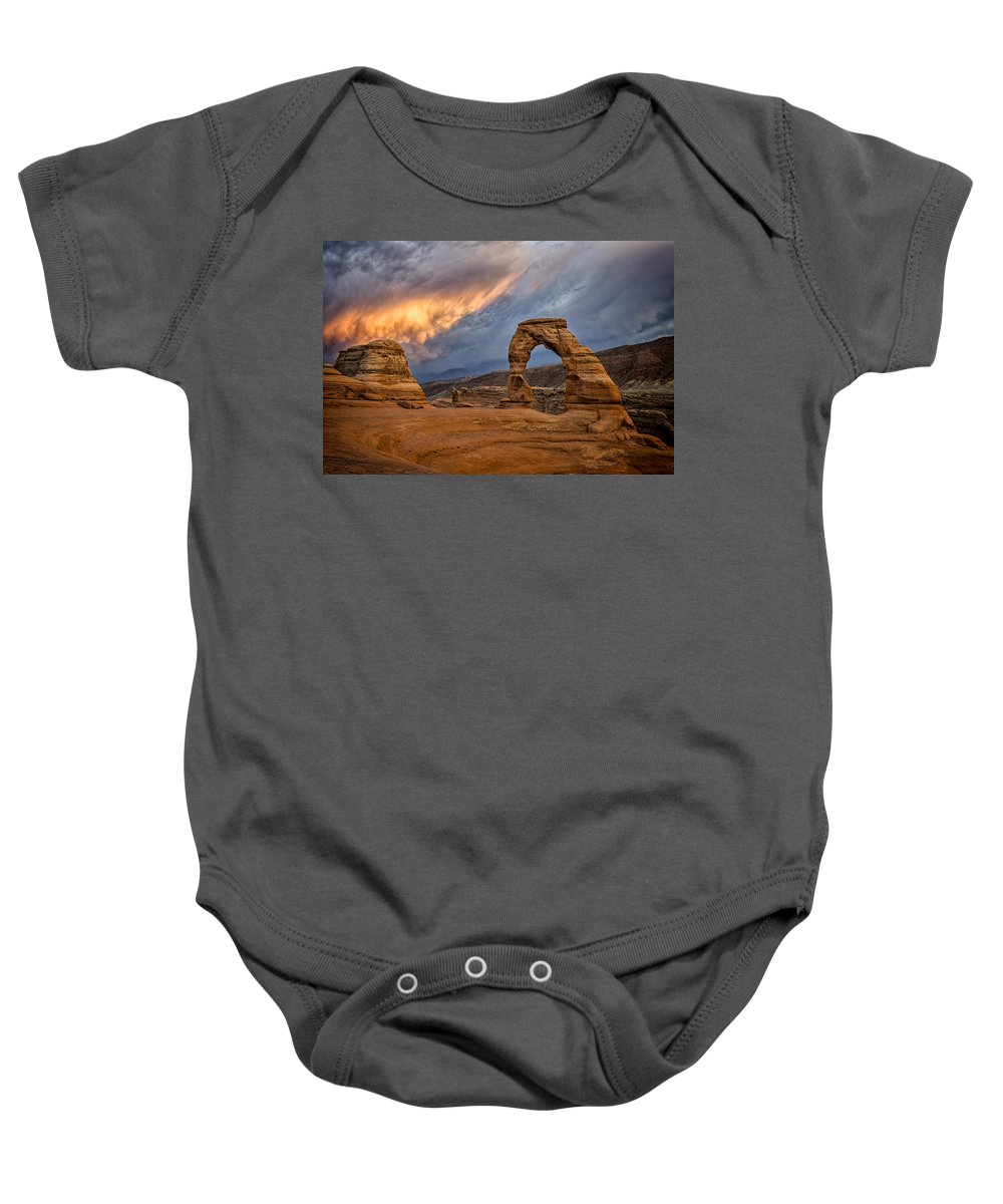 Delicate Arch Baby Onesie featuring the photograph Fire In The Sky by Jeff Burton
