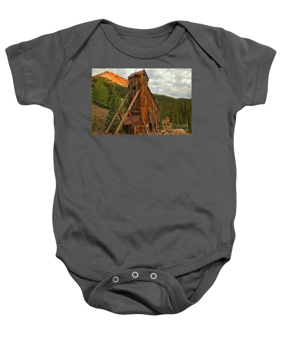 Yankee Girl Mine Baby Onesie featuring the photograph Glowing Under The Storm Clouds by Adam Jewell