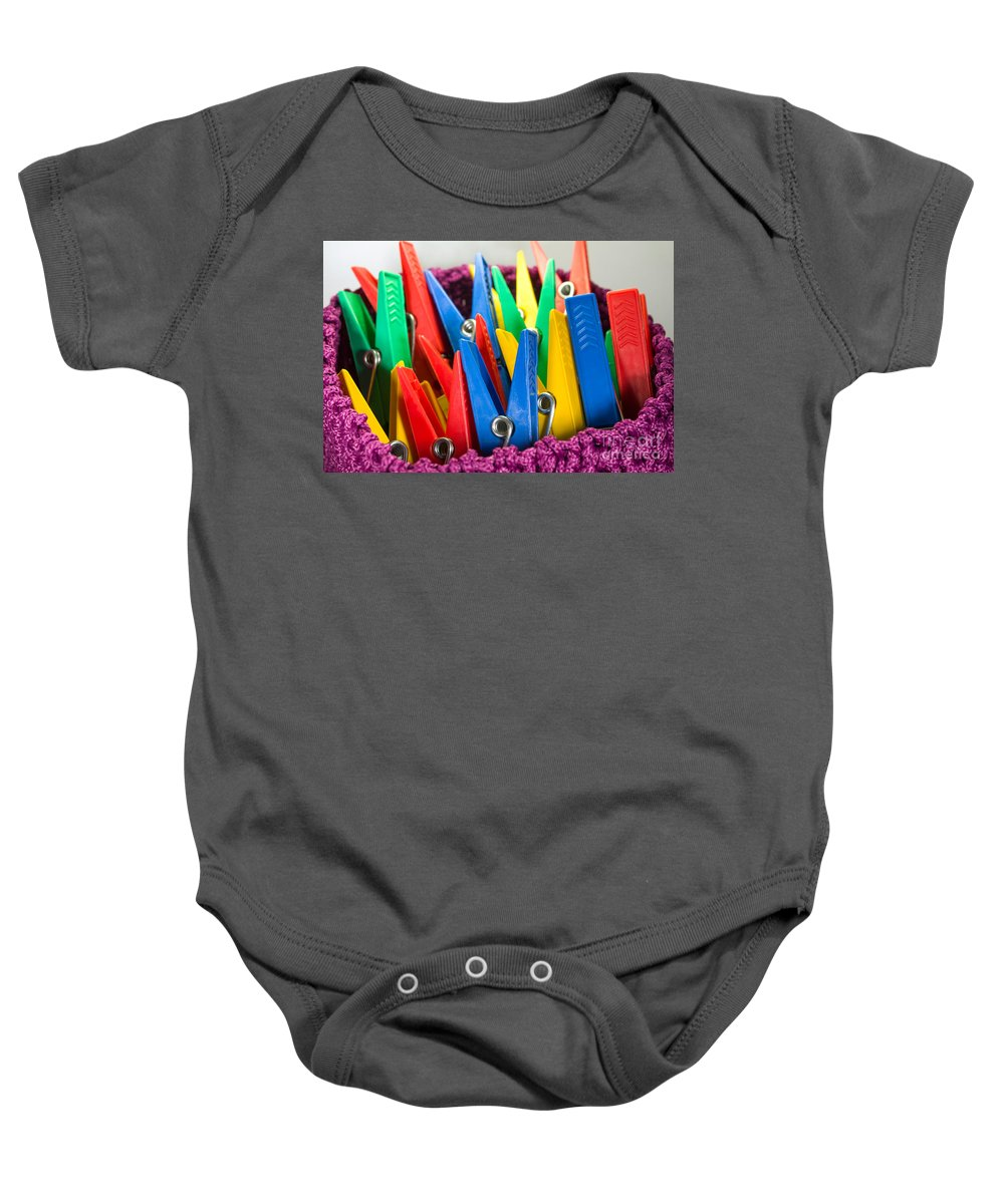Basket Baby Onesie featuring the photograph Group Of Colorful Clothespins by Ferenc Kosa