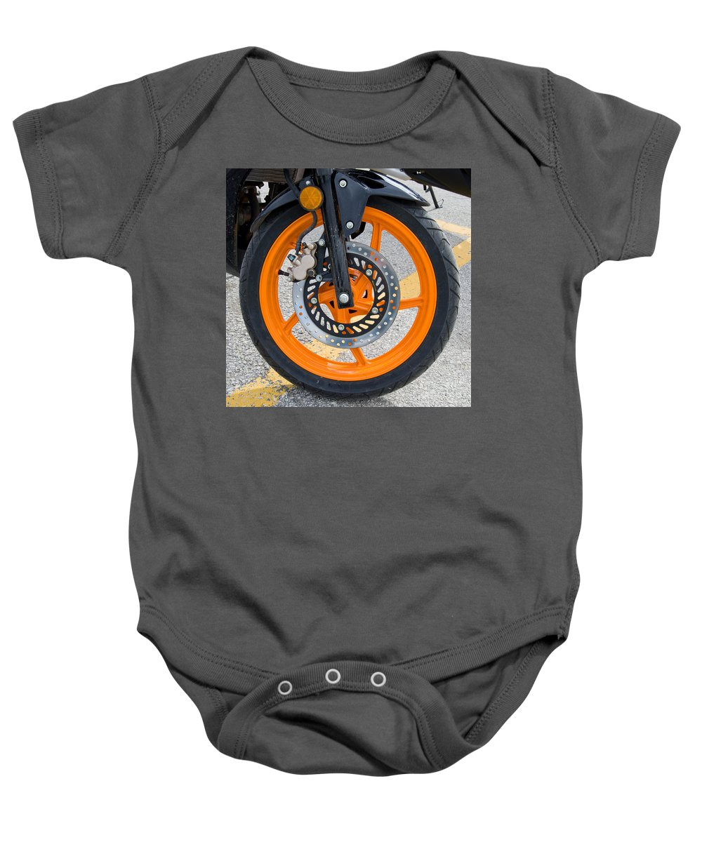 Asphalt Baby Onesie featuring the photograph Motorcycle Wheel by Les Palenik