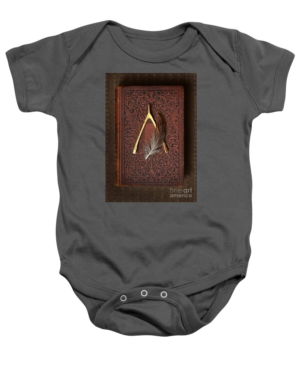 Wishbone Baby Onesie featuring the photograph Wishbone And Feather On Antique Book by Jill Battaglia