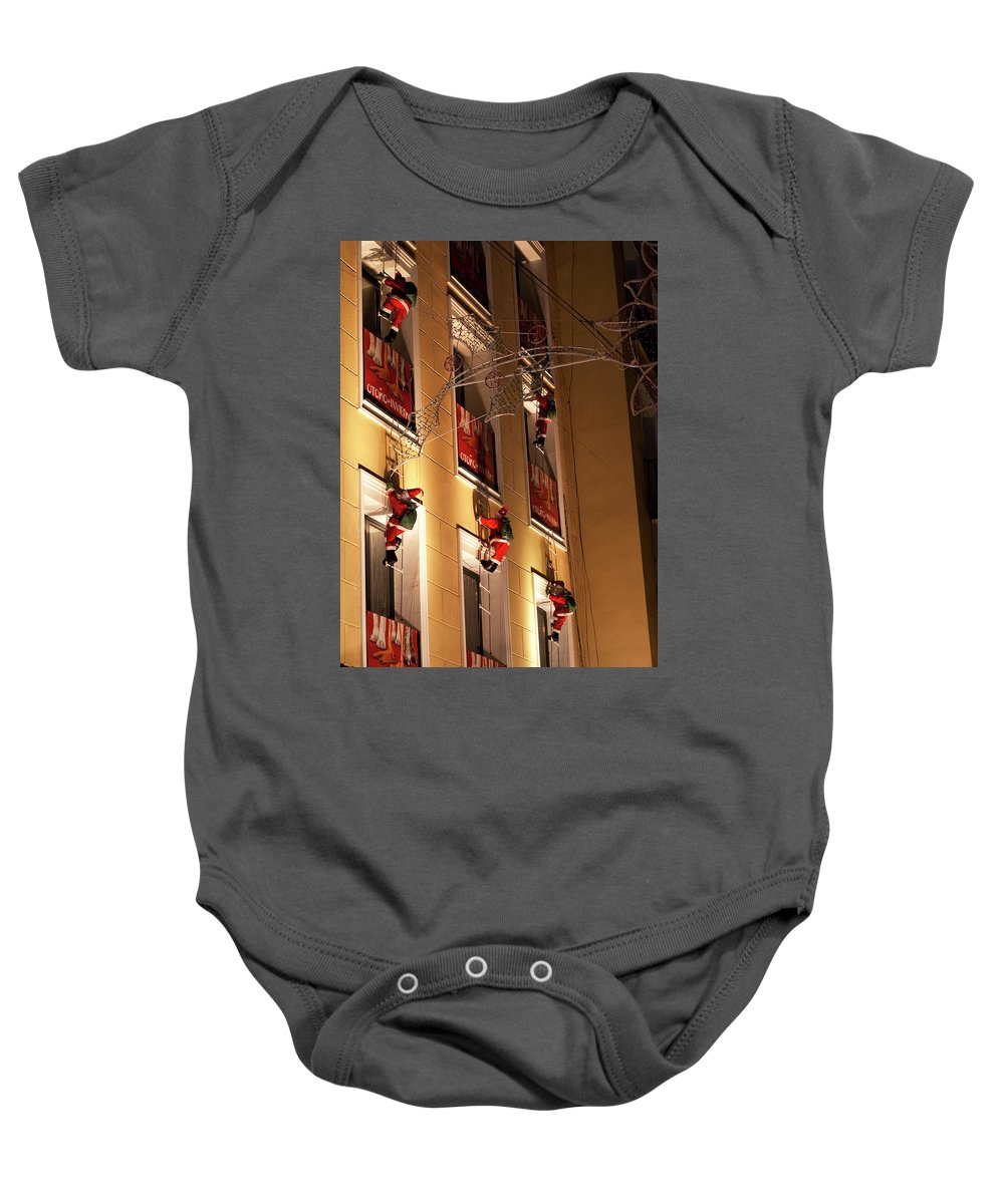 Madrid Baby Onesie featuring the photograph A Wall Of Sneaky Santas by Lorraine Devon Wilke