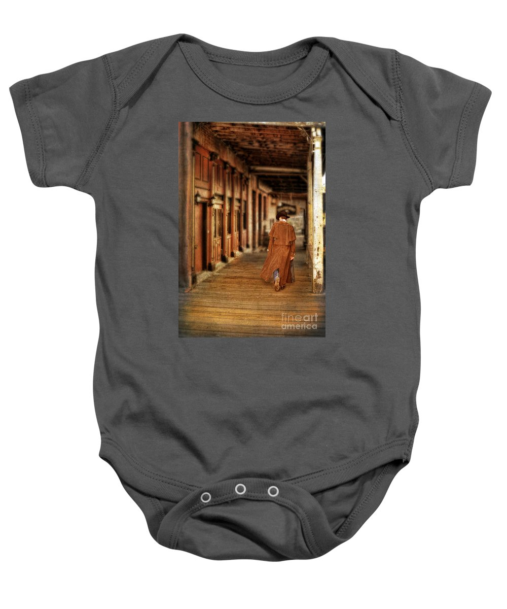 Cowboy Boots Baby Onesie featuring the photograph Cowboy In Old West Town by Jill Battaglia