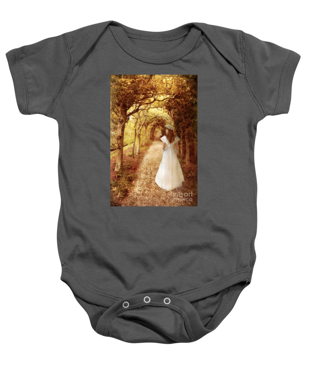 Woman Baby Onesie featuring the photograph Lady Walking In Tree Tunnel In Garden by Jill Battaglia