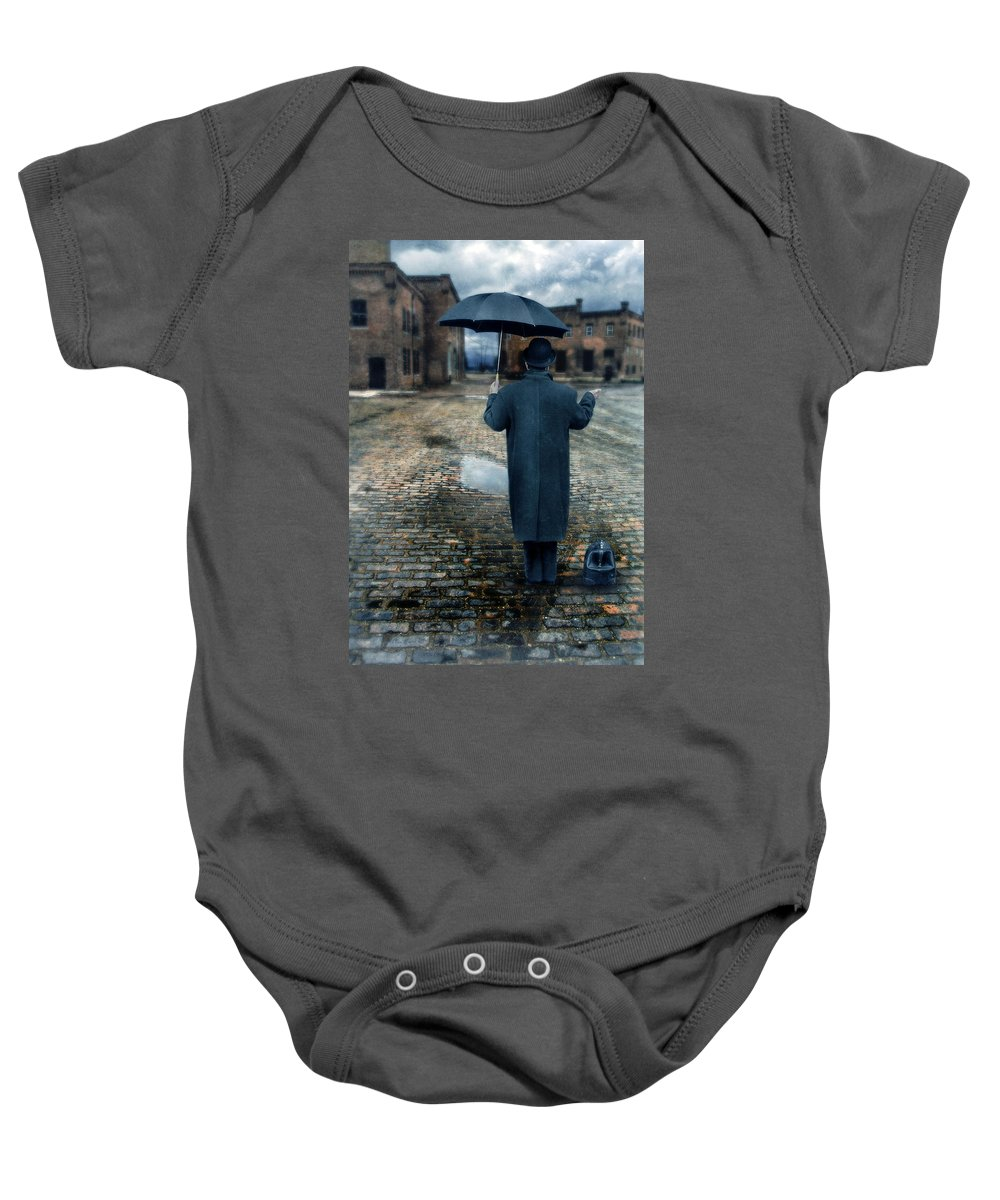 Man Baby Onesie featuring the photograph Man In Vintage Clothing With Umbrella On Rainy Brick Street by Jill Battaglia