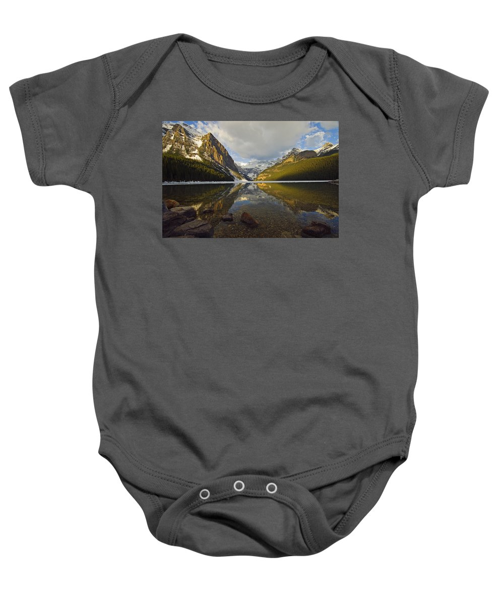 Calming Baby Onesie featuring the photograph Mountains Reflected In Lake Louise by Mike Grandmailson