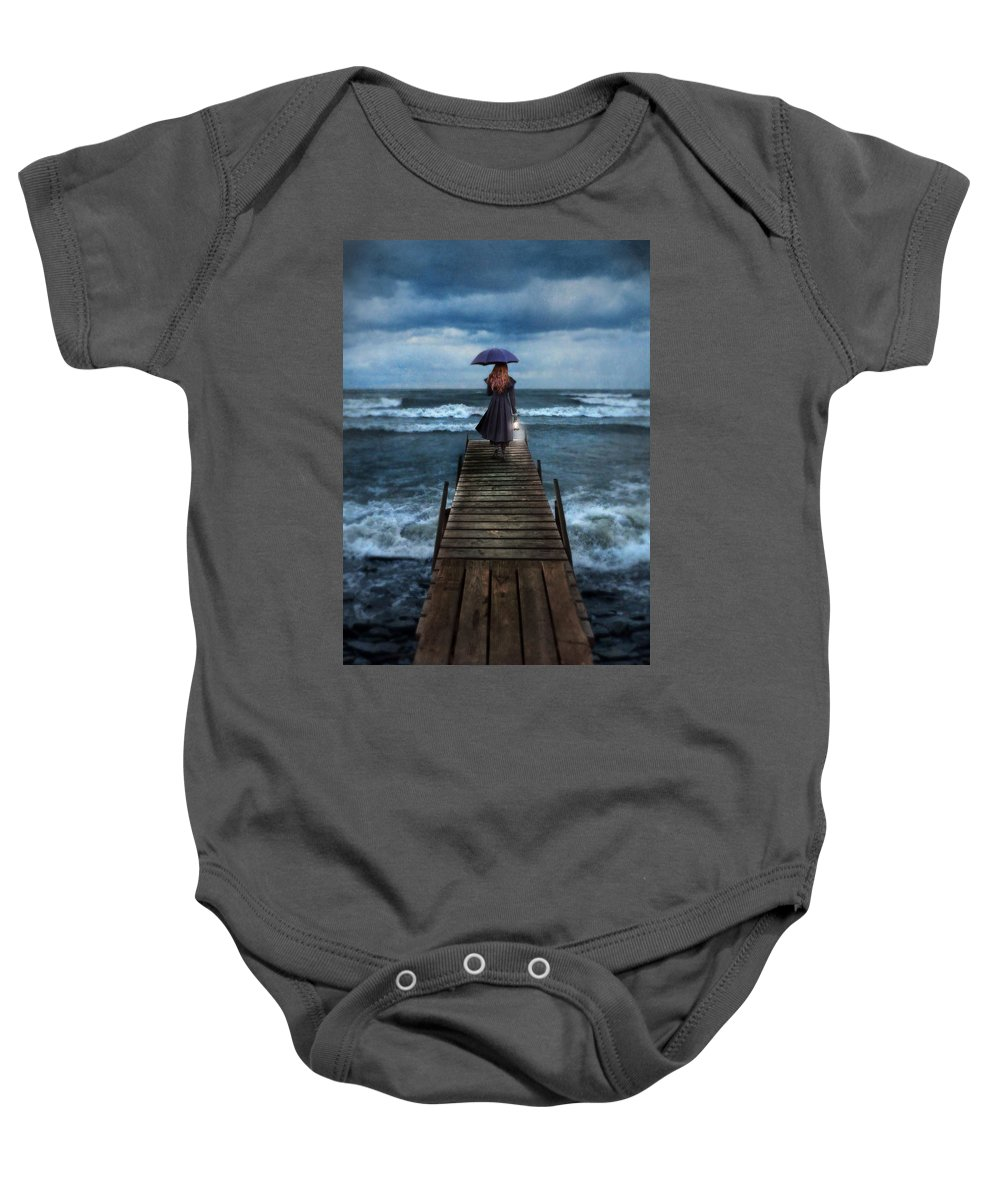 Woman Baby Onesie featuring the photograph Woman On Dock In Storm by Jill Battaglia