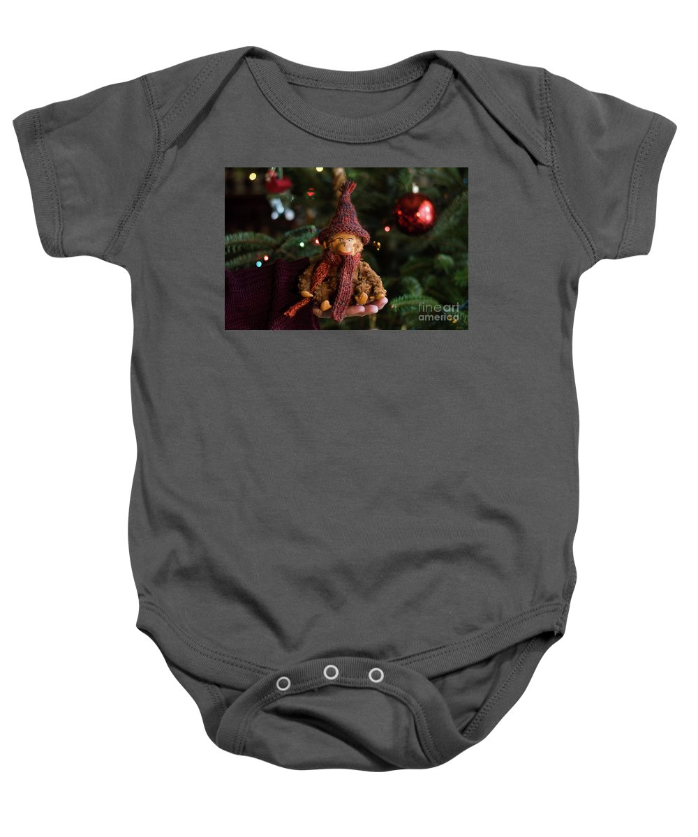 Monkey Baby Onesie featuring the photograph Silly Old Monkey Toy In A Child Hands Under The Christmas Tree by Andrea Varga