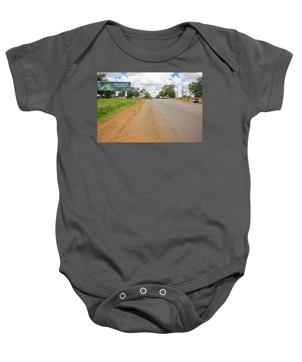 Road Baby Onesie featuring the photograph Welcome Sign To Lilongwe In Malawi. by Marek Poplawski