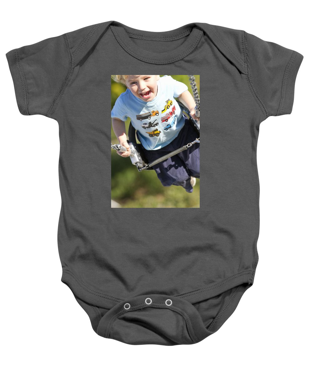 Light Baby Onesie featuring the photograph Young Boy Smiling Swinging In A Swing by Robert Postma