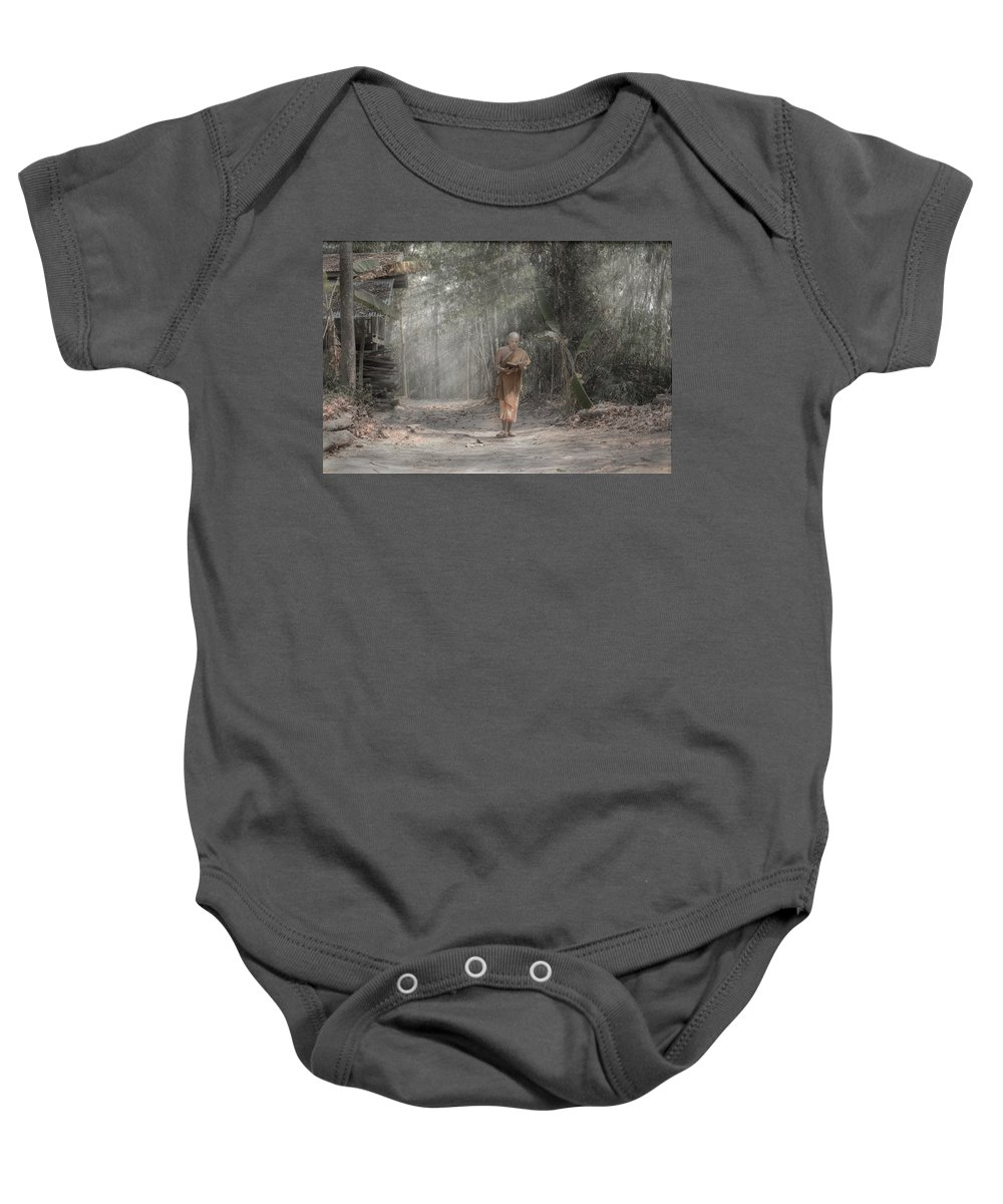 Monk Baby Onesie featuring the photograph A Monk Reading by Nopphol Nasuwan
