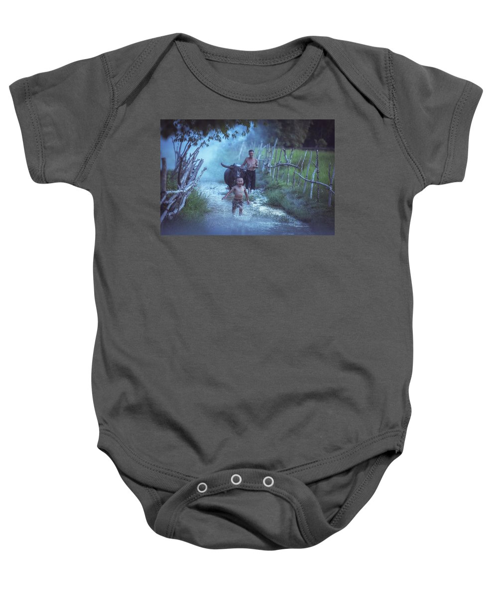 Running Baby Onesie featuring the photograph Asian Boy Playing Water With Dad And Buffalo by Somchai Sanvongchaiya