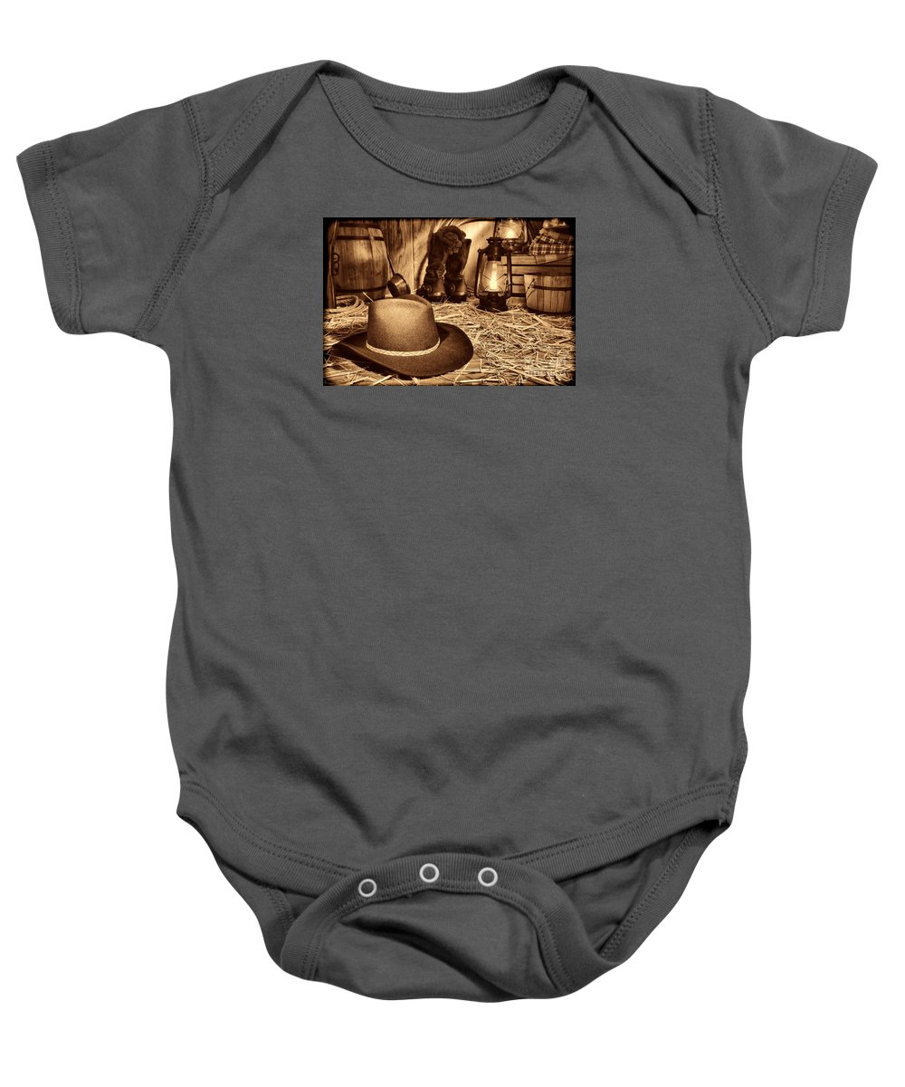 Western Baby Onesie featuring the photograph Black Cowboy Hat In An Old Barn by American West Legend By Olivier Le Queinec