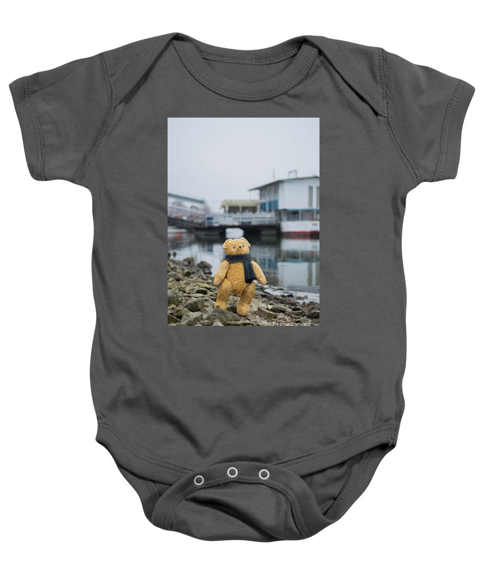 Animal Baby Onesie featuring the photograph Cheerful Teddy Bear In Knitted Scarf Stand By The Riverside Beside The Port by Andrea Varga