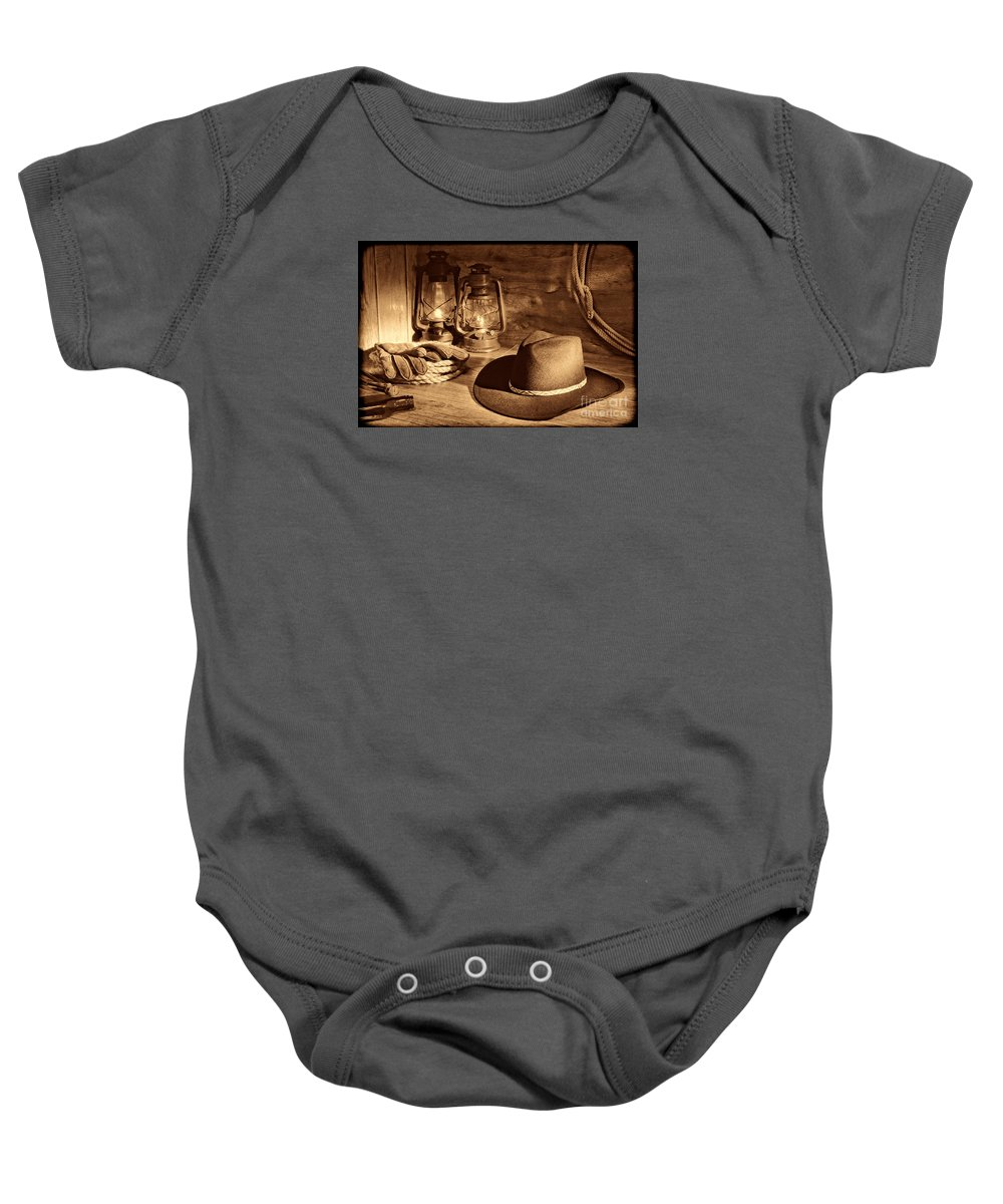 Western Baby Onesie featuring the photograph Cowboy Hat And Kerosene Lanterns by American West Legend By Olivier Le Queinec