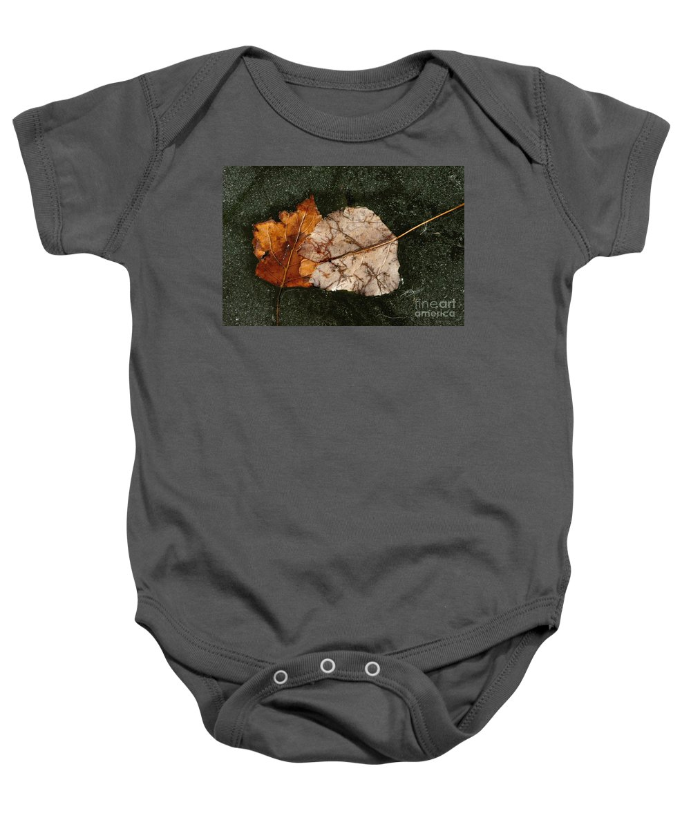 Fallen Leaves Baby Onesie featuring the photograph Fallen Leaves On Frozen Water by Merrimon Crawford
