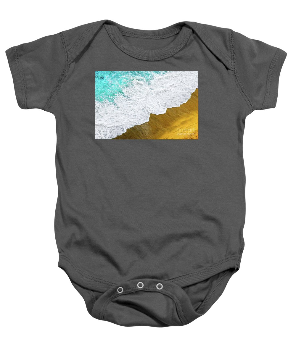 Water Baby Onesie featuring the photograph Footsteps In The Sand Hopelessly Facing The Rising Tide by Silvia Ganora