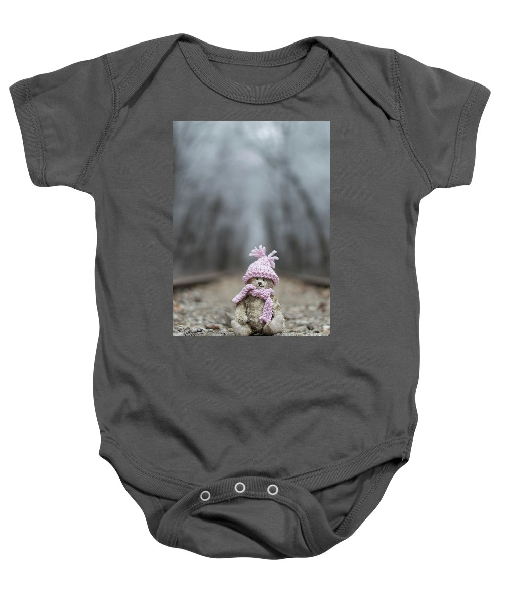 Teddy Baby Onesie featuring the photograph Little Teddy Bear Sitting In Knitted Scarf And Cap In The Winter Forest Between The Rails by Andrea Varga