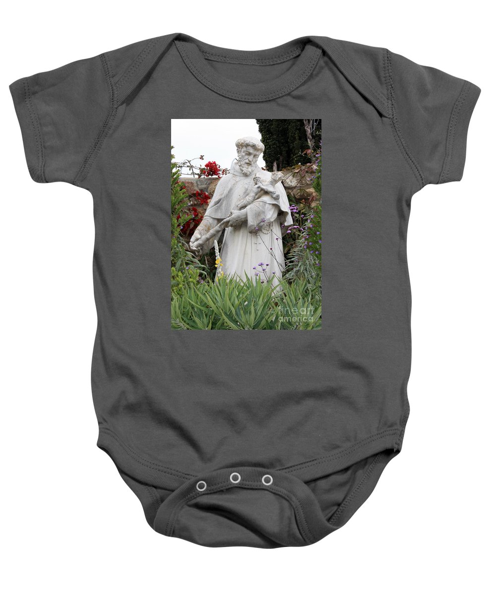 Saint Francis Baby Onesie featuring the photograph Saint Francis Statue In Carmel Mission Garden by Carol Groenen