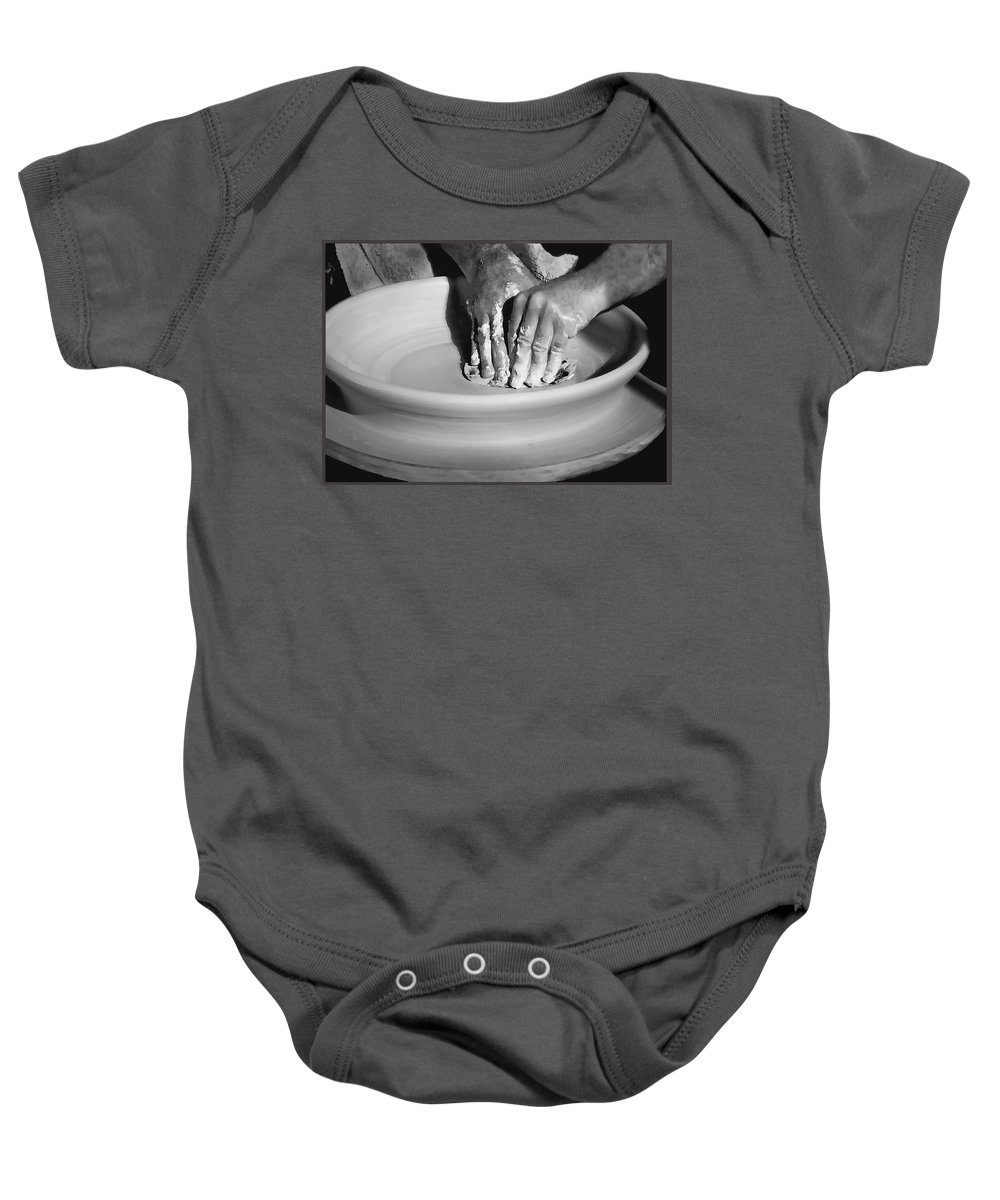 Hand Baby Onesie featuring the photograph The Potter by Sharon Foster