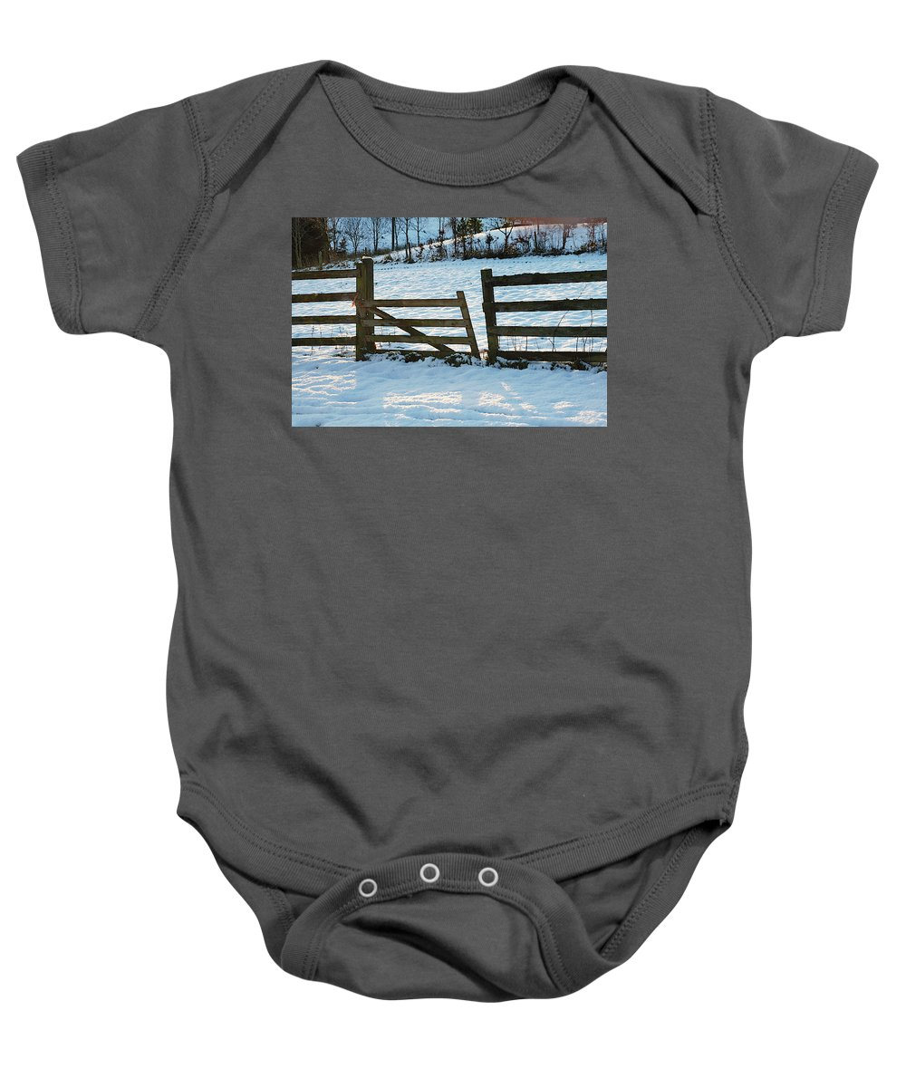 Snow Baby Onesie featuring the photograph Broken Fence In The Snow At Sunset by Victor Lord Denovan