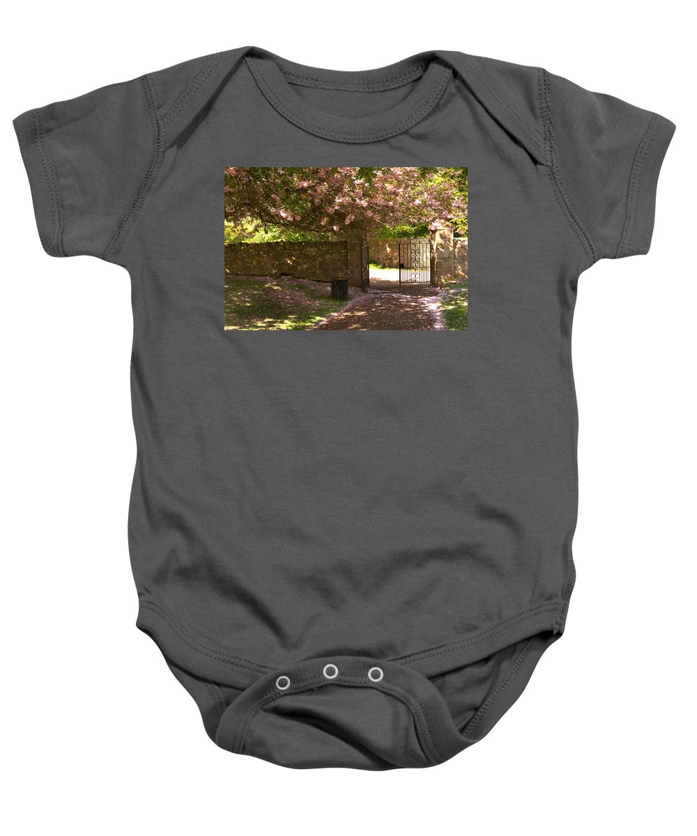 Walls Baby Onesie featuring the photograph Crichton Church Entrance Gate And Tree In Pink Bloom by Victor Lord Denovan