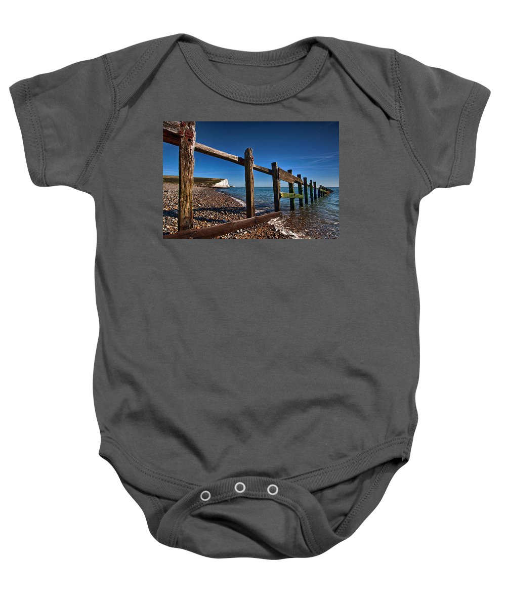 Cuckmere Baby Onesie featuring the photograph Seven Sisters Through Sea Defences by Dave Godden