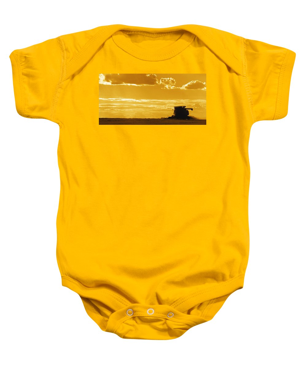 Field Baby Onesie featuring the photograph Field With Combine At Sunset by Darren Greenwood