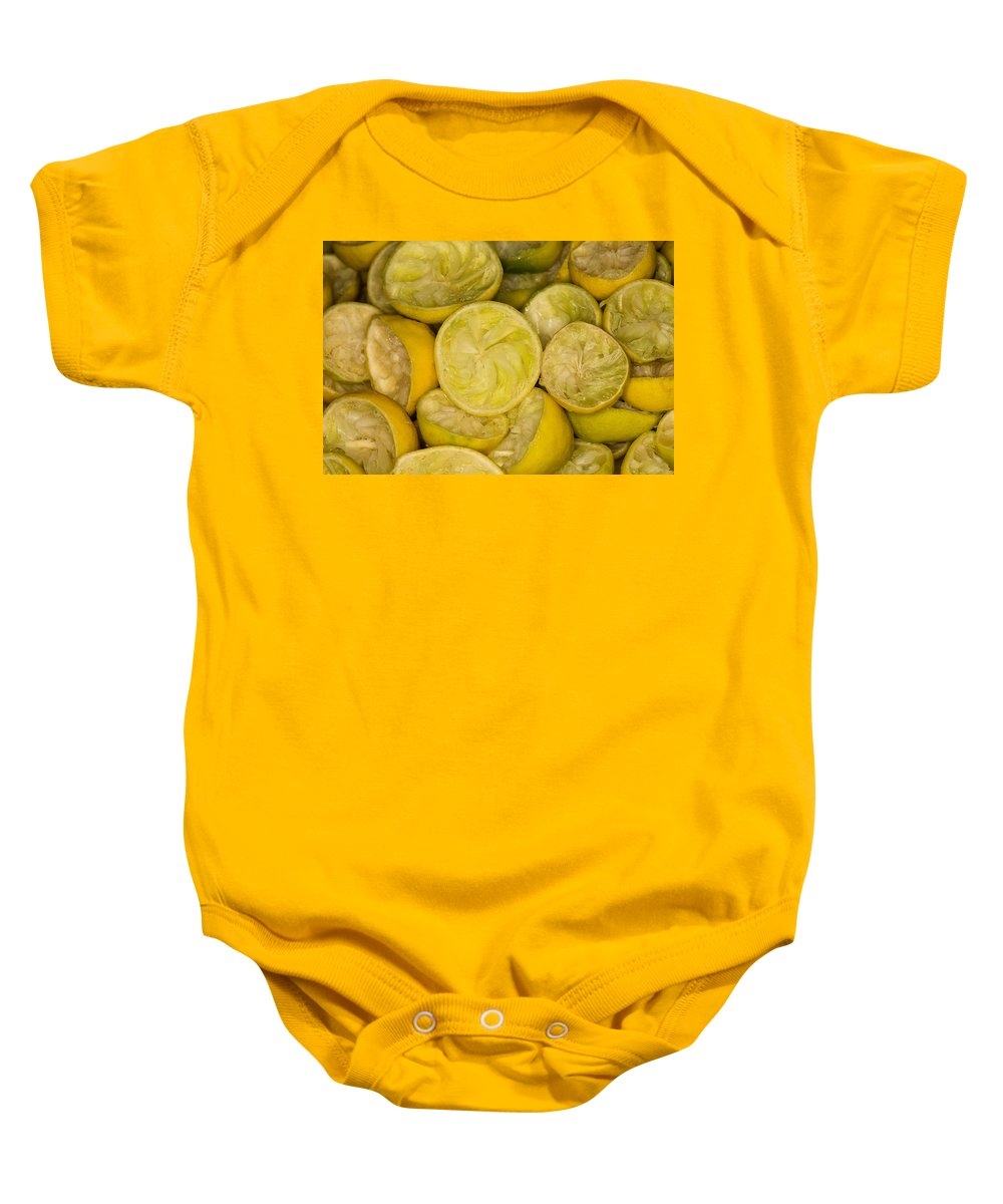Absence Baby Onesie featuring the photograph Squeezed Key Lime Halves by Diane Macdonald