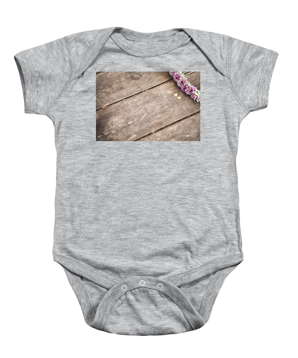 Simplicity Baby Onesie featuring the photograph Flower Frame On On Wood Background by Gal Eitan