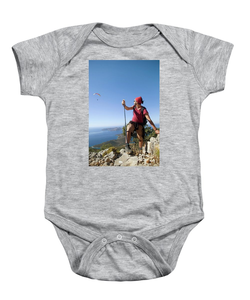 Antalya Baby Onesie featuring the photograph A Male Climber Looking At Paragliding by Me Studio