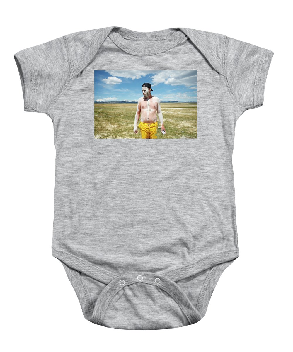 25-29 Years Baby Onesie featuring the photograph A Mans Face Covered In Clay Mud by David Zentz