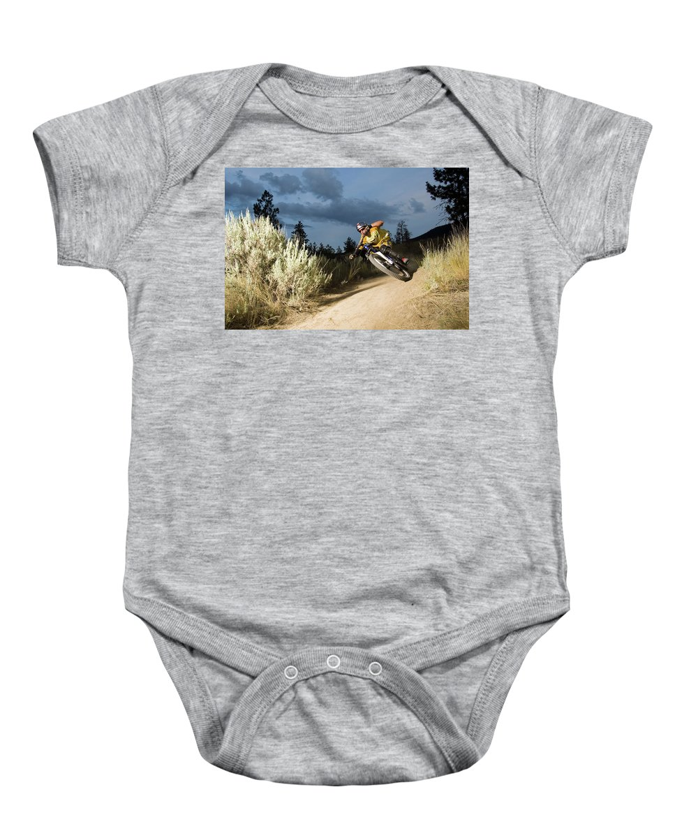 Bicycle Baby Onesie featuring the photograph A Mountain Biker Rides A Trail by Blake Jorgenson