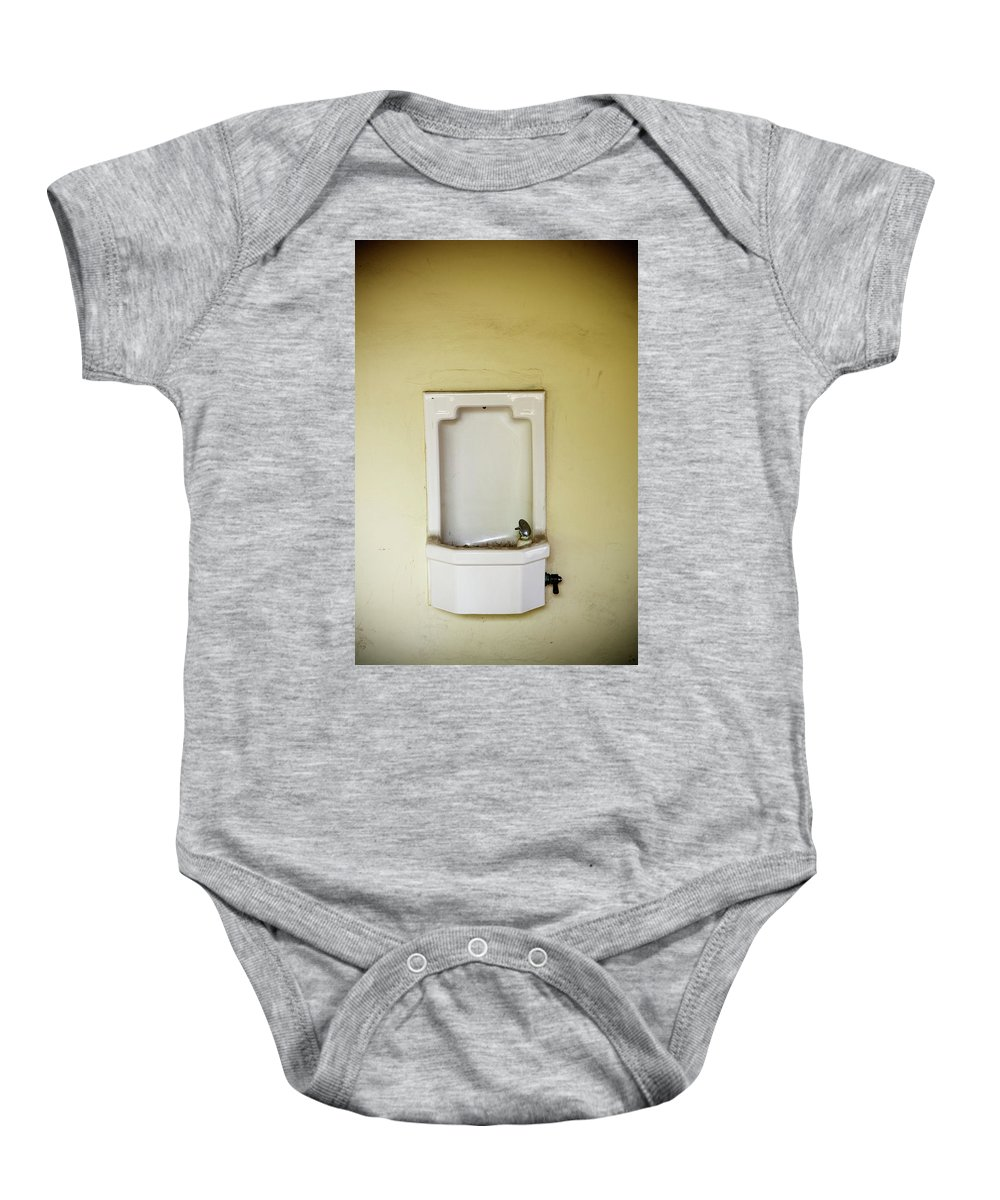 Absence Baby Onesie featuring the photograph A Porcelain Wall Mounted Drinking by Ron Koeberer